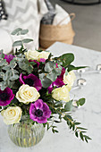 Bouquet of white roses, purple anemones and eucalyptus