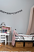 Garland of lettering on grey wall above bed and dolls' house