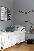 Bed with valance below garland of letters on grey wall