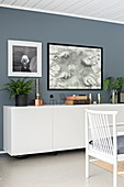 Vintage ornaments on floating sideboard on grey wall