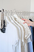 Hand picking lace blouse on hanger from suspended clothes rail