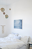 Mobile made from globes above bed in white bedroom