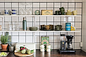Green cups and old tins on kitchen shelves above worksurface