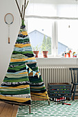 Teepee handmade from strips of fabric in child's bedroom