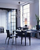 Black dining table in loft apartment with industrial windows and stone floor