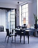 Schwarzer Esstisch in einem Loft mit Fabrikfenstern und Steinboden