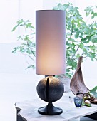Table lamp with tall cylindrical lampshade and spherical base