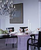 Kronleuchter über festlich gedecktem Tisch mit rosa Läufern