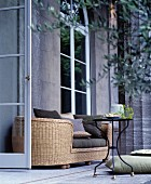 Oval rattan sofa and metal table outside Classical house
