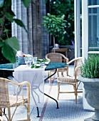 Sitzplatz im Säulengang mit rundem Tisch und Korbstühlen