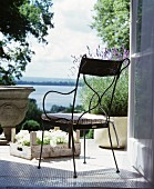 Metal chair and lavender on terrace with view of lake