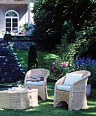 Wicker furniture in shady seating area in classic summer garden