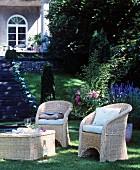Schattiger Sitzplatz mit Korbmöbeln im klassischen Sommergarten