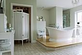 Free-standing bathtub on platform in vintage-style bathroom