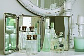 Collection of vintage-style perfume bottles in front of mirror