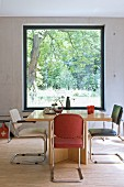 Retro cantilever chairs around wooden table in front of panoramic window