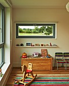 Rocking horse in child's bedroom with narrow horizontal window