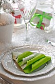 White place setting with green paper napkin folded into Christmas tree amongst artificial snow on table
