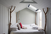 Bed with branches used as corner posts in tiny house with wood-clad walls