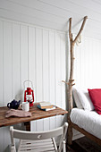 Chair and table next to bed with branch used as bedpost
