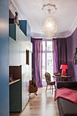 Blue cabinets in small guest room with purple walls