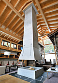 Fireplace below suspended chimney in architect-designed, Alpine house