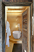 View into wood-clad bathroom through rustic wooden door