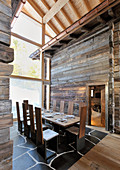 Long set dining table between two mountain huts incorporated into architect-designed house