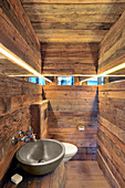 Narrow mirrored strip running along three rustic wooden walls in bathroom