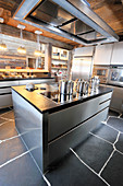 Modern stainless steel kitchen with slate floor in wooden house