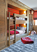 Transparent chair in front of fitted bunk beds with red striped back wall