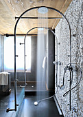 Rainfall showers fitted on arched pipes next to stone wall clad in white pebbles