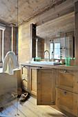 Offene Tür am Waschbeckenunterschrank im Bad aus Holz