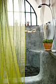 Green curtain in front of masonry shower area with organic shapes