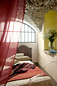Bed below arched window and vaulted stone ceiling