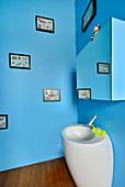 Pedestal sink with organic form in bright blue bathroom