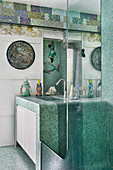 Washstand covered in green mosaic tiles in bathroom