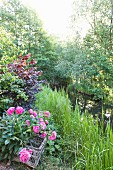 Idyllic stream with bushes, trees and basket of flowering peonies on bank