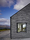 Grey stone façade of modern house with view in through window