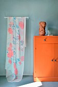 Delicate floral fabric hanging next to orange cabinet