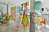 Woman hanging fabrics from line in loft apartment with columns and colourful eclectic furnishings