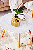 Gold-colored flower vase with a leaf on a coffee table with a marble top