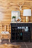 Vintage Kommode mit offenen Fächern, darauf Tischleuchte mit goldfarbenem Lampenfuß und Spiegel, vor Wand mit Holzverkleidung