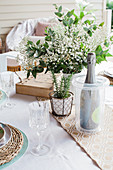 Champagne cooler with champagne bottle and bouquet of flowers on laid table