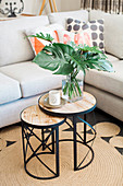 Two-part side table with lantern and philodendron leaves in front of upholstered furniture