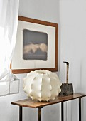Framed picture above lampshade and sculpture on vintage table