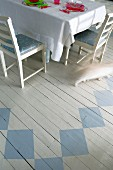 Set table on white wooden floor painted with geometric pattern