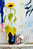 Sunflower in blue vase next to elegant sequinned hat and feminine shoe horn in front of painting