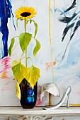 Sonnenblume in blauer Vase neben elegantem Pailetten-Hütchen und femininer Schuhlöffel vor Gemälde