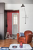 Leather armchair under wall-mounted lamp next to open doorway leading into hall